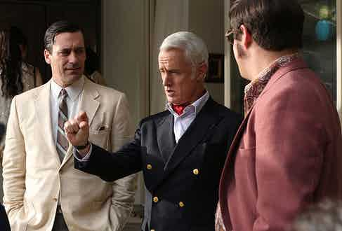 Roger Sterling's nautical-inspired navy double-breasted blazer polished off with a rakish red neckerchief and a shock of white hair.