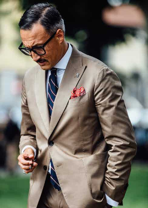 Double handmade backstitching runs down the length of the lapel, darts and pockets. As with the snug armhole, this hand-finished effect is impossible to achieve using a machine. This gentleman wears a bright pocket square in the 'barchetta' outbreast pocket. Photo by Jamie Ferguson.