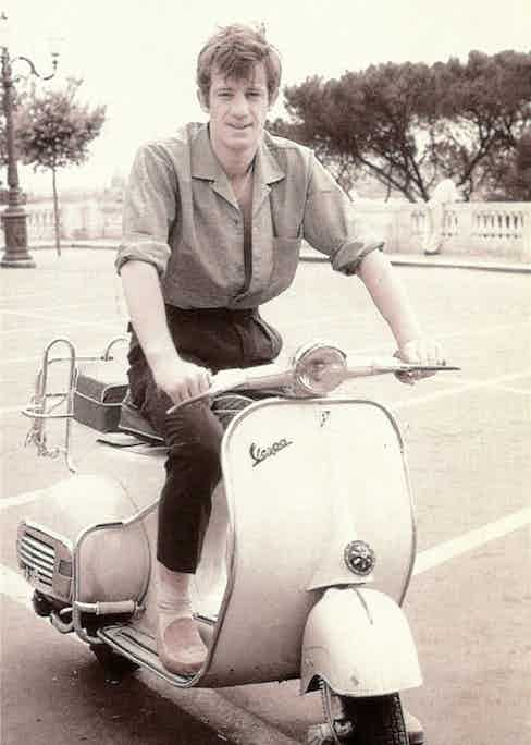 Jean-Paul Belmondo displaying his Riviera credentials with high-waisted, pleated trousers, a tucked in camp collar shirt, loafers and a Vespa, circa 1960s.