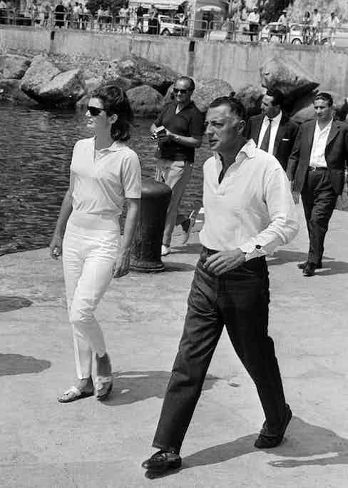 Godfather of the Cote d'Azur, Gianni Agnelli is pictured with Jackie Kennedy as they stroll along a pier in the Amalfi Coast, 1962.