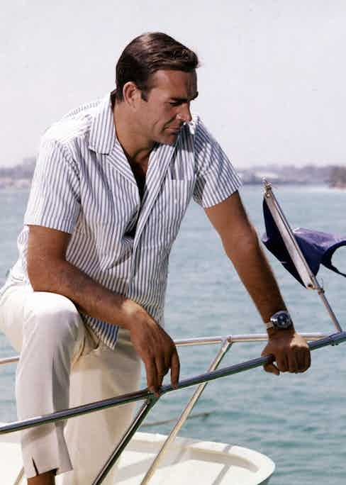 Connery's Bond wearing a Bengal-striped, camp collar shirt with white trousers that feature a distinct slit at the hem. Notice also Bond's Breitling Top Time wristwatch, which famously featured a geiger counter, as fitted by Q Branch. Connery is pictured on the set of Thunderball in Nassau, the Bahamas in 1965.