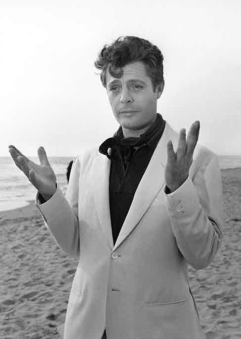 Marcello Mastroianni embodied Riviera style in 1960's La Dolce Vita, here pictured on the beach with a white suit, black shirt and neckerchief combination.