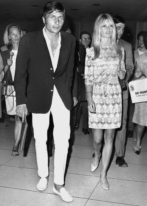 A quintessential Riviera look by Gunter Sachs, featuring his signature white trousers, a low-buttoned shirt, a soft, dark blazer and white loafers. He's pictured with Brigitte Bardot, circa 1960s.