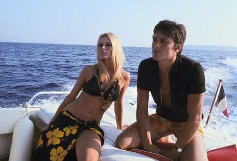 Alain Delon displaying the style credentials of the polo shirt aboard a yacht with Brigitte Bardot, circa 1960s.