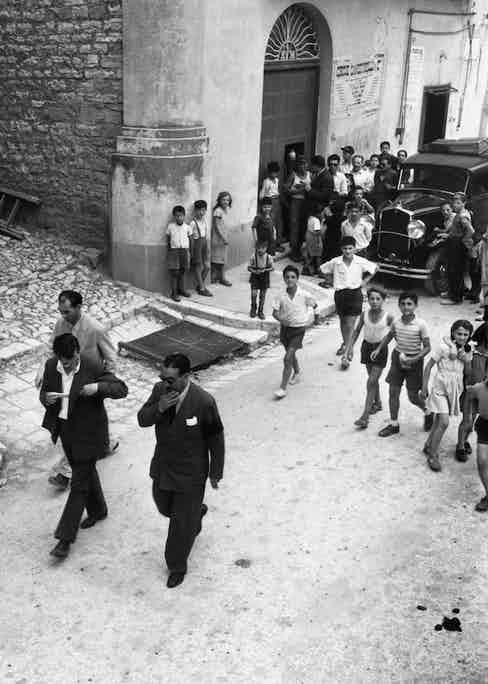 Exiled Mafia boss Charles 'Lucky' Luciano and entourage draw a crowd, mainly of children, as they walk down a street in Sicily, 1949. Photo by Slim Aarons/Getty Images.