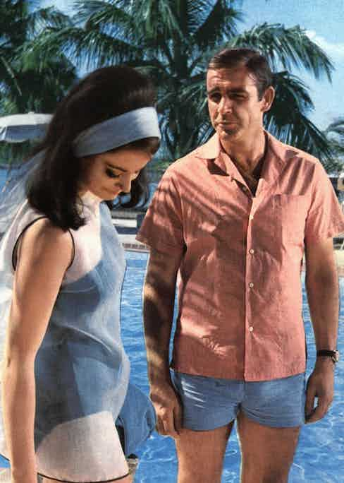 Despite being more well known for his tailoring, Connery's Bond had an enviable resort wardrobe, including this short-sleeve camp collar shirt and swim short combination, worn alongside Claudine Auger in Thunderball, 1965.