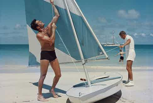 Slim Aarons' photograph 'Boating in Antigua', showing two ways to wear swim shorts, circa 1960s.