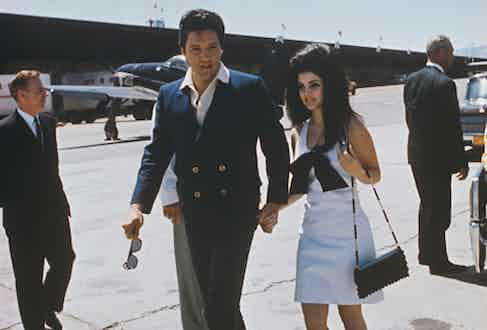 Elvis Presley with Priscilla Presley at an airport during their honeymoon from Las Vegas to Palm Spring, 1967.
