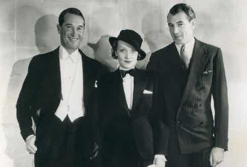 Gary Cooper shows his ability to pull off the double-breasted jacket, despite the fabric pulling and the balance of the suit being a little off. On a tall character like Cooper, the suit would benefit from a double vent in the skirt and higher pockets on the hip. He's pictured with Maurice Chevalier (left) and Marlene Dietrich (centre). Photo by Moviestore/REX/Shutterstock.