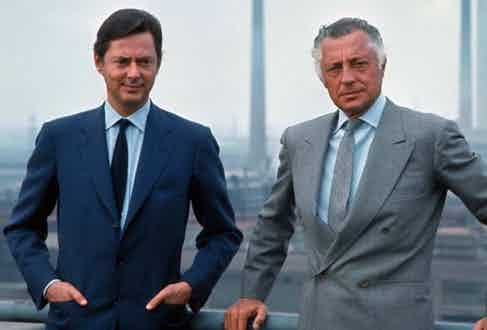 The blue-grey double breasted suit (right) is a 4x1 design. The left lapel appears to be draping openly, suggesting that the jigger is undone even on this jacket, a style Agnelli carries off with aplomb. Here, he poses with his brother in 1968.