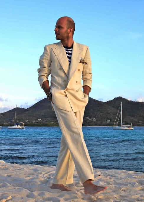 Luca Rubinacci brings his family house's Neapolitan sprezzatura to a double-breasted off-white suit. The rolling lapel over a casual striped crew neck and pushed up sleeves emits confidence and ease.
