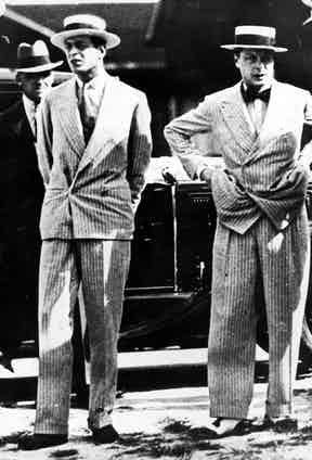 The Duke of Kent (left) with his brother the Duke of Windsor (right) wearing similar suits cut from the same chalkstripe fabric, yet worn in different ways. The Duke of Windsor (right) wears a 6x2 jacket closed with both buttons done up. In contrast, the Duke of Kent (left) wears a similarly cut coat but with just the bottom button fastened. A 4x2 rolled to the lower button (with the top buttons placed directly above the bottom) became known as the 'Kent' style, after the Duke repeatedly wore his suits in this way. Photo by Keystone/Getty Images.