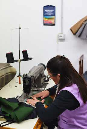 One of Ambrosi's craftspeople closes the exclusive trouser. Photo by James Munro.