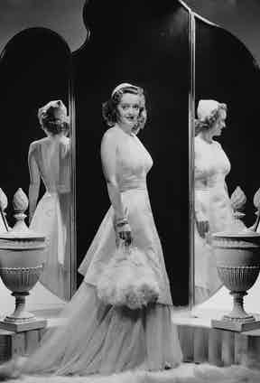 Three shades of Bette: posing in front of an elaborate mirror, circa 1930s.