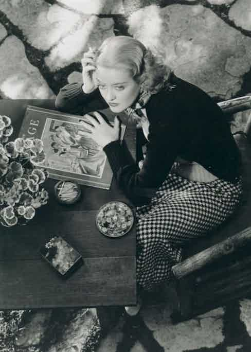 Relaxing in a houndstooth skirt and black cardigan, circa 1930s. Photo by Moviestore Collection/Rex Features.