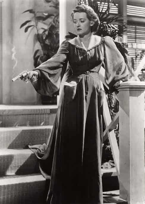Holding a commanding pose with a smoking gun on the set of The Letter, 1940.