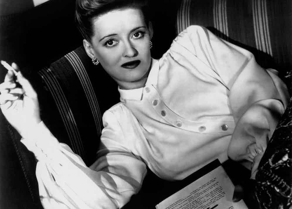 Elegantly reading whilst smoking a cigarette on the set of Now Voyager, 1942.