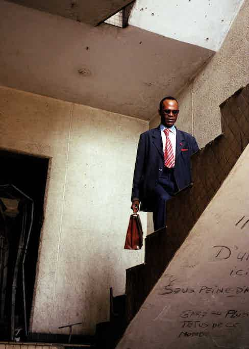 Yves Francois Ngatsongo, also known as Yves Saint Laurent, is the president and founder of the France Libre association. He walks up the stairs of the storey building were he lives in downtown. This building, along with others - damaged by the combats of the last civil war, 1997-2001 - have been squatted in for some time.