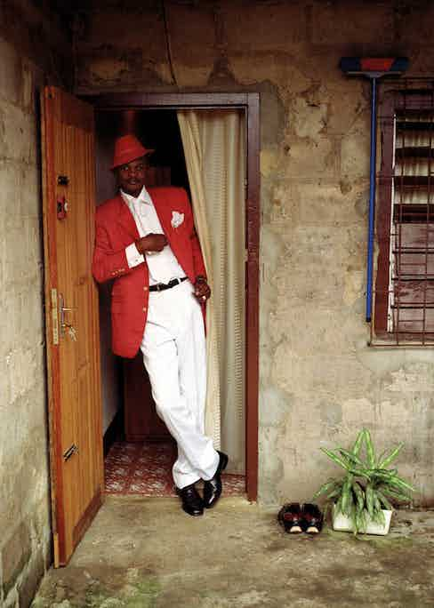 The sapeur Delagrace, also known as the Icon of Beautiful Colours, in the doorway of his rented room.