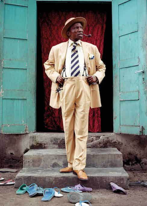 Severin Mouyengo, who has been a sapeur since the seventies, poses in the entrance of his family house in the Bacongo neighborhood. Sandals on the ground are from his family members. In the Congo, as in other parts of Africa, people often take their shoes off before entering home.