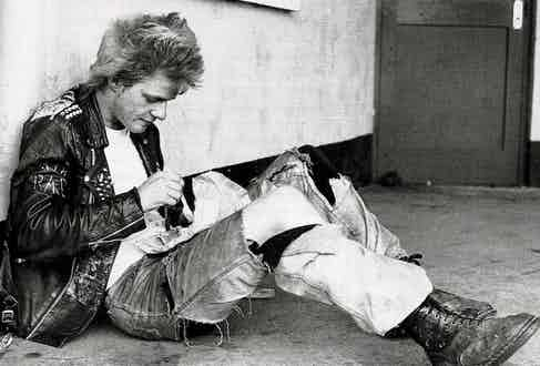 The picture of Britain in the 1980s; a punk eats fish and chips from a newspaper in his Dr. Martens, ripped jeans and studded leather jacket.