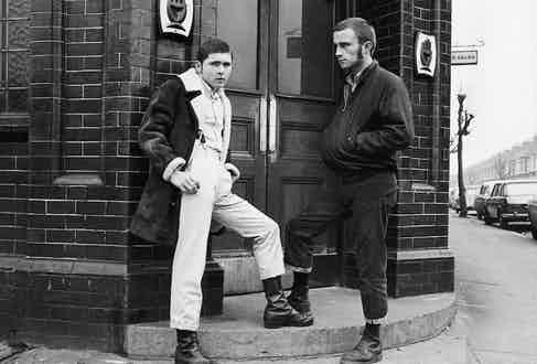 Two British skinheads in London in 1970. The man on the right sports Dr. Martens, turn-up selvedge denim jeans and a dark Harrington jacket.