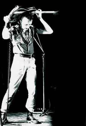 Joe Strummer of The Clash wears Dr. Martens on stage, photographed by Pennie Smith, circa 1980.
