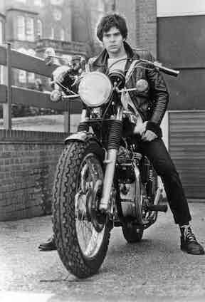 The Stranglers' bass player JJ Burnel, a keen wearer of black 1460s, rides a Triumph Bonneville in Manchester, 1979.