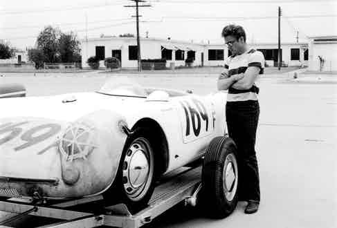 Admiring someone else's Porsche 550 Spyder at a rally, a car that he would shortly after acquire, in 1955. Photo by Collection Christophel/Alamy.