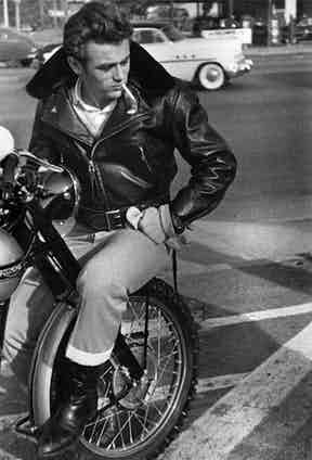Wearing his leather biker jacket whilst sitting on the front tyre of his Triumph, circa 1955.
