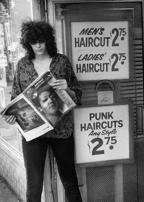 Joey Ramone stands outside a hairdresser that specialises in 'Punk Haircuts' reading a copy of Long Island Pulse magazine with Aretha Franklin starring on the cover, circa 1968.