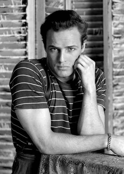 Brando poses in a nautical striped T-shirt worn with high-waisted trousers, circa 1960.