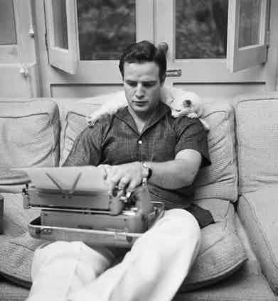 Relaxing at home with a typewriter and his cat, whilst wearing an open-collar, short-sleeved shirt and wide-legged trousers, circa 1955.