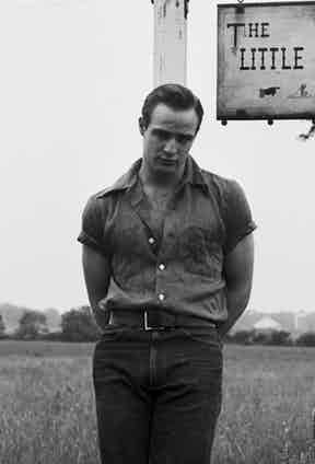 Wearing a short sleeved shirt with the sleeves rolled up, high-waisted denim jeans and a well-honed scowl outside his home in the Hollywood Hills, Los Angeles, 1952.
