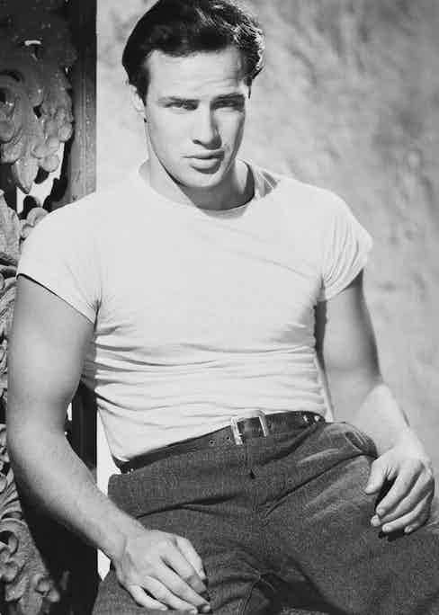 As character Stanley Kowalski in the film A Streetcar Named Desire, 1951. Brando's T-shirts in the film were unusually tight for the era, displaying more of the male physique than had been seen in mainstream cinema previously.