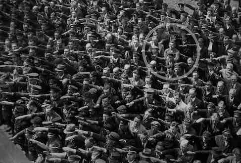 August Landmesser (circled) deliberately crossed his arms instead of saluting, in defiance to Hitler and the Nazi regime, 1936.