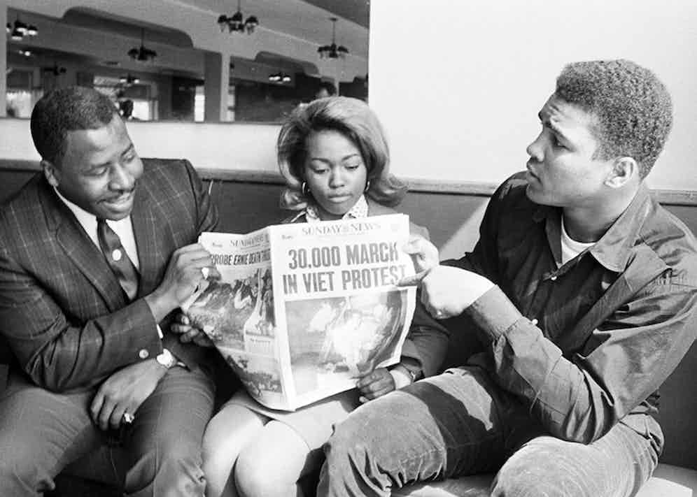 Boxing champion Muhammad Ali refused to be inducted into the U.S. Army and was immediately stripped of his heavyweight title. Here, he can be seen passionately discussing a newspaper with the headline, '30,000 march in Viet Protest', in 1967.