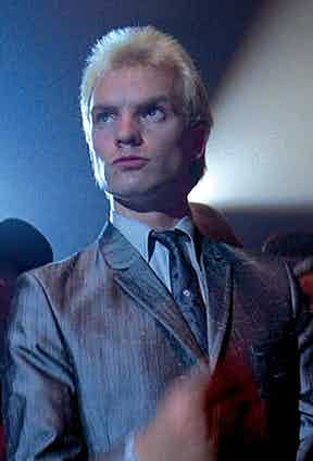 Sting as 'Ace Face' wearing a silver/grey, three buttoned suit in a mohair blend, with a visible tie pin. Photo by Alamy.