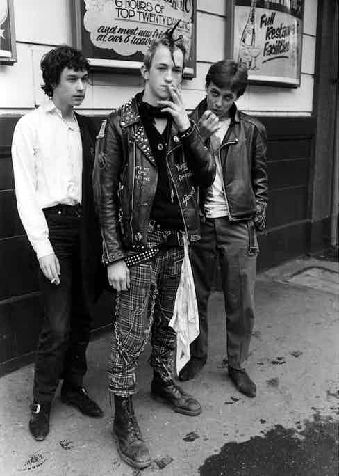 A punk smokes a cigarette in lace up DMs, tartan trousers and a leather jacket, 1981. Photo by Peter Price/REX/Shutterstock.
