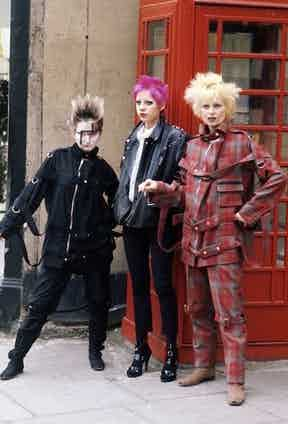 Vivienne Westwood leans against a telephone box with fellow punks in London, 1977, wearing her notorious tartan bondage suit. Image © Corbis.