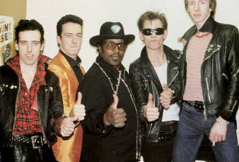 The Clash and Bo Diddley on tour in 1979. Left, Mick Jones sports a dishevelled tartan shirt with the collar turned up, tucked into a chunky leather belt and leather trousers.