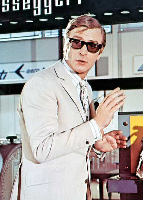 Michael Caine completes a '60s ensemble of a beige linen suit and striped shirt, a pocket square and tortoiseshell sunglasses in The Italian Job, 1969. Photo by Everett Collection Inc/Alamy.