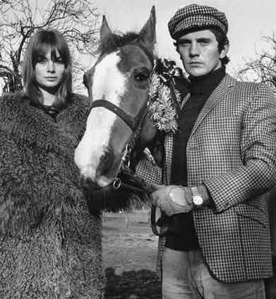 Actor Terence Stamp poses with fashion model Jean Shrimpton sporting a matching houndstooth check tweed jacket and cap paired with a roll-neck sweater, 1965. Photo by Terry Disney/Express/Getty Images.