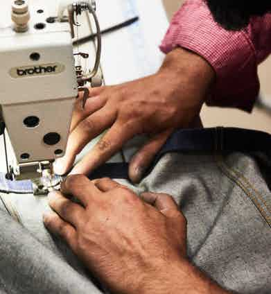 Stitching a pair of jeans together. Photo by Kim Lang.
