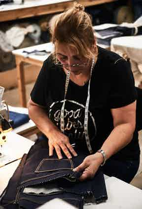 Inspecting the rear pockets. Note the lacking waistband, which is stitched on towards the end of the jean-making process. Photo by Kim Lang.