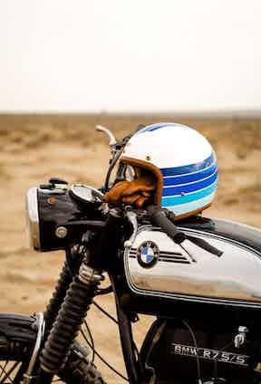 The custom BMW with a Hedon x The Rake Apollo helmet resting on its fuel tank.