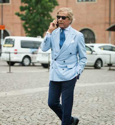 Proprietor of Al Bazar in Milan, Lino Ieluzzi can be seen wearing a signature outfit of his consisting of a light blue 6x2 double-breasted jacket, dark blue trousers and a number '7' tie.