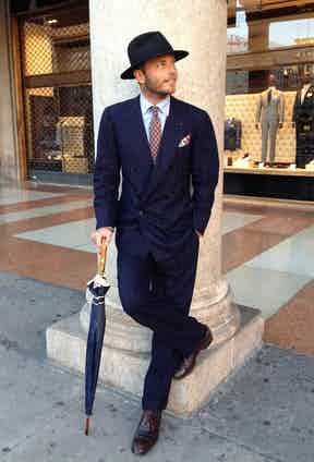Luca Rubinacci sporting a vintage-inspired chalkstripe 6x1 double-breasted suit, combined with a wide-brim fedora and a wodden-handle umbrella.