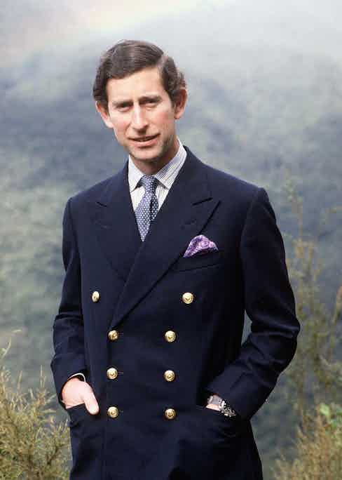 Prince Charles wearing his signature 8x3 double-breasted blazer, finished with gold buttons that nod to the style's military origins.
