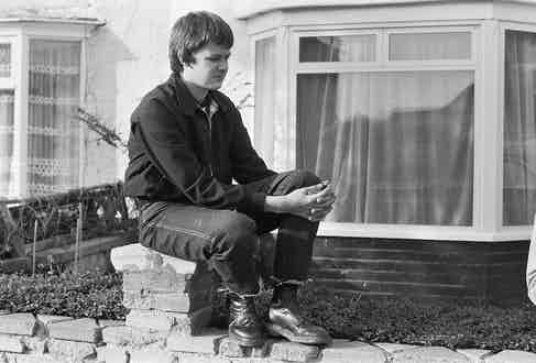 A British teenager wearing frayed denim jeans, heavy work boots and a Harrington jacket - the uniform of the skinhead - in 1980. Photo by Mark Charnock/PYMCA/REX/Shutterstock.